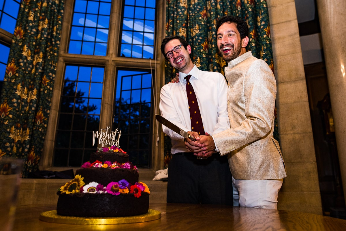 Wedding guests mockingly pose to cut the cake at Rhodes House photo