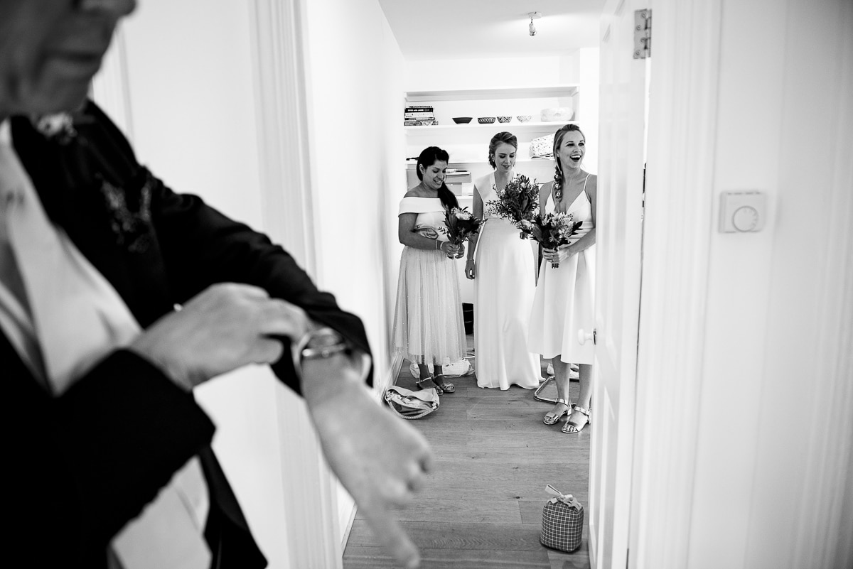 father of the bride checking his watch as the bridesmaids get ready