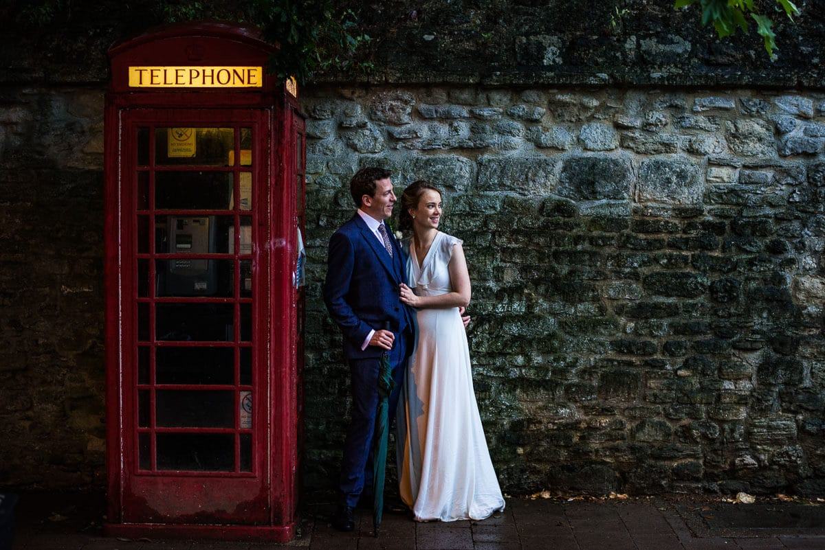 Bride and groom stand next to a red telephone box In Oxford