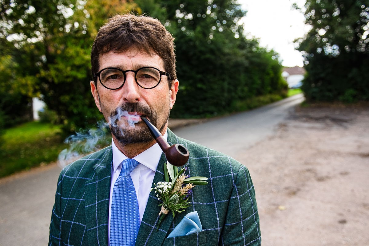 wedding guest smoking a pipe detail