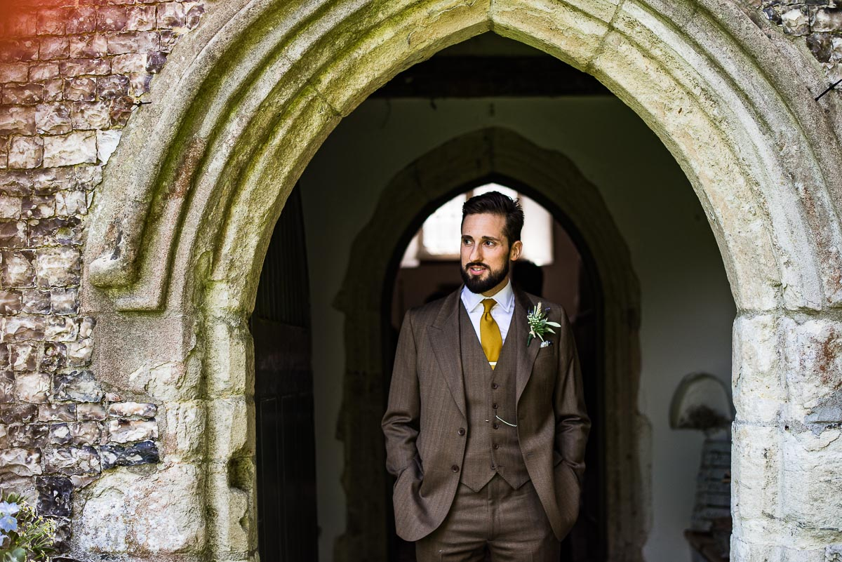 groom poses under small brick arch