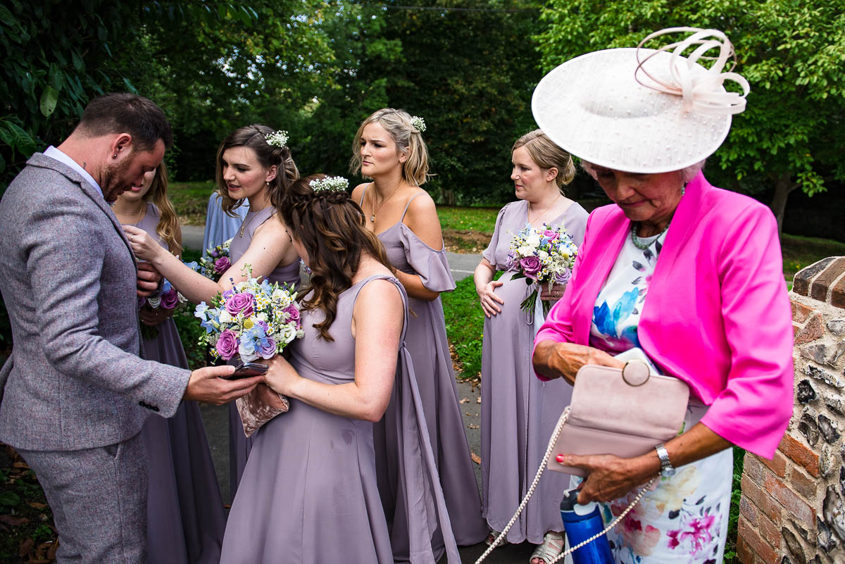 bridesmaids gather and adjust wedding guests suit