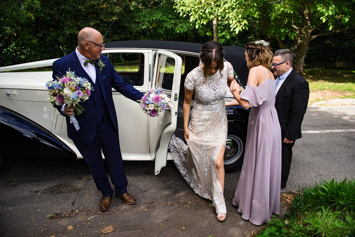bridesmaid and father of the bride help bride out of car