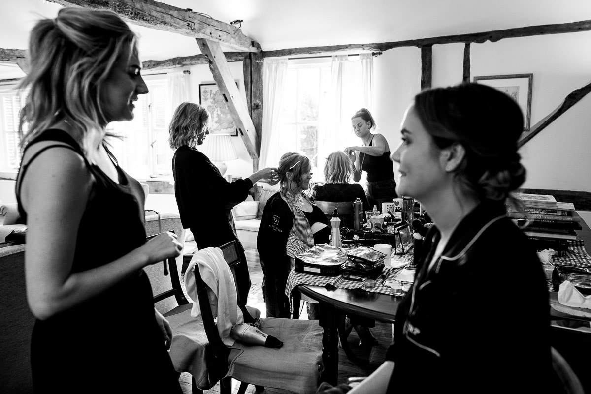 wedding guests and bride preparing and getting their makeup done