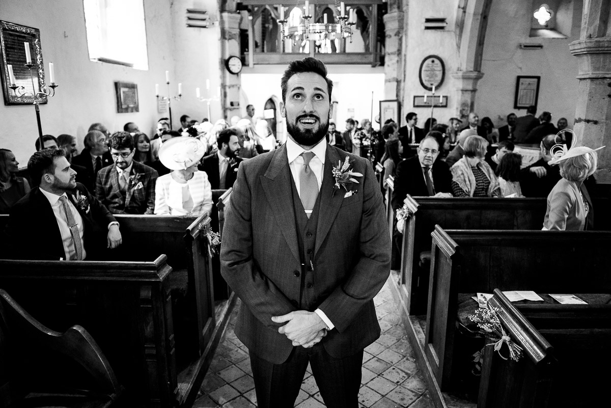 groom waits patiently at alter for bride to arrive