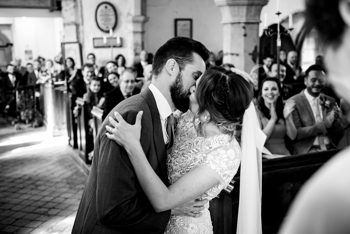 bride and groom finally kiss earning an applause from wedding guests