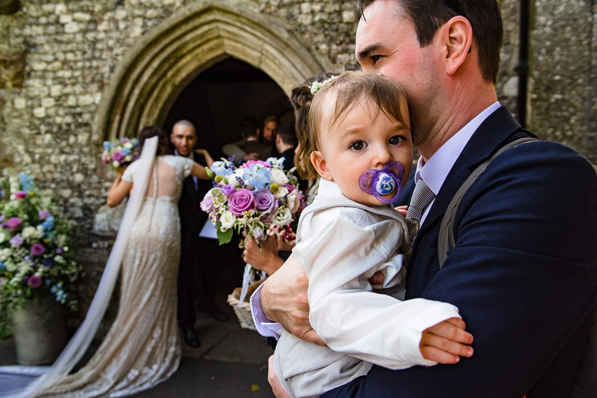 wedding guest holds small baby as bride enters venue detail