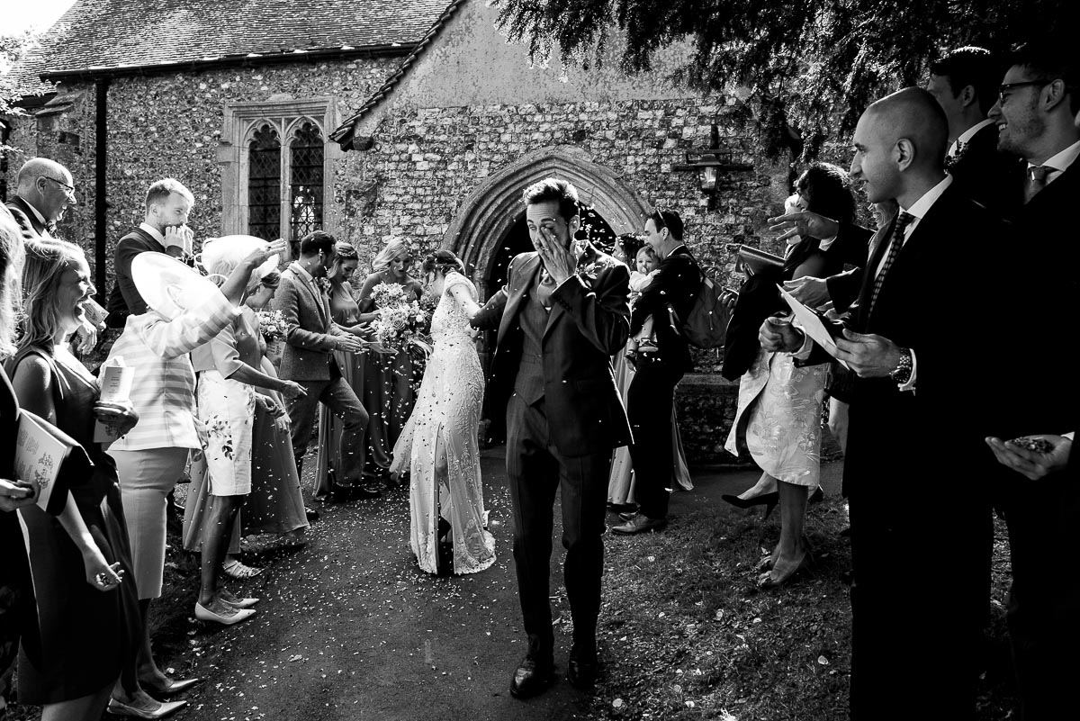 groom rubs confetti out of his eye as the guests celebrate