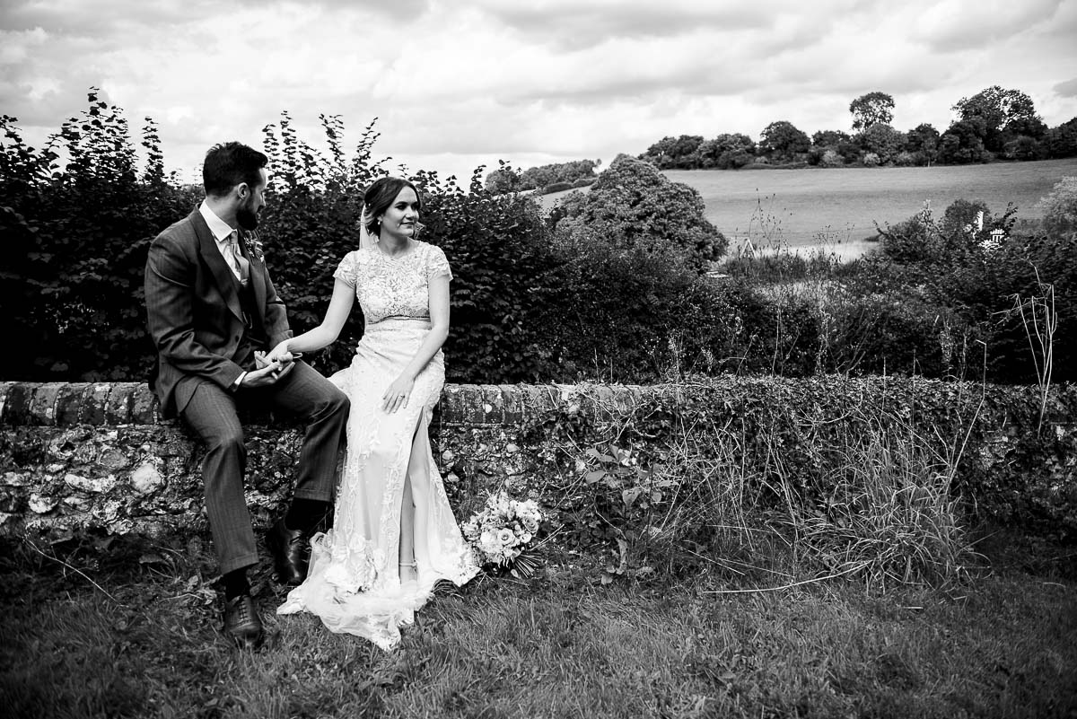 bride and groom sit together and gaze at the countryside a Court Lodge