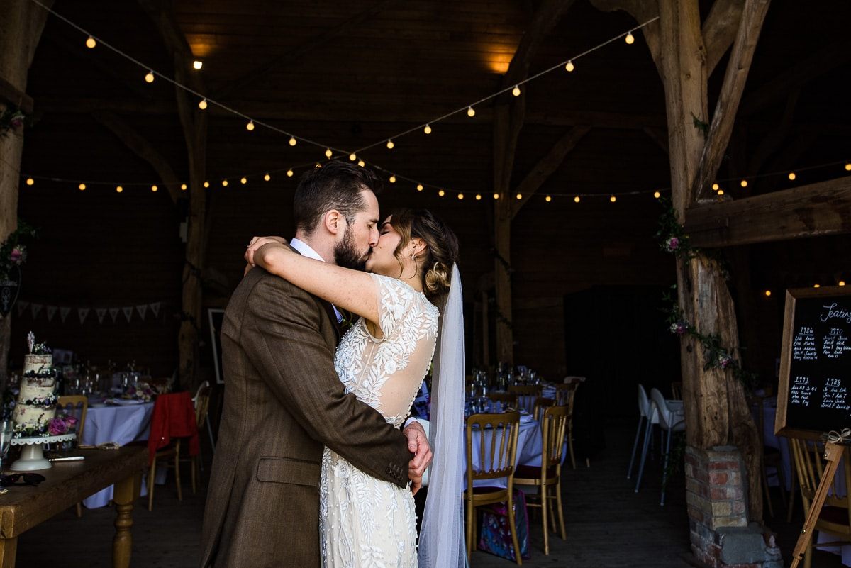 bride and groom embrace and kiss under fairy lights