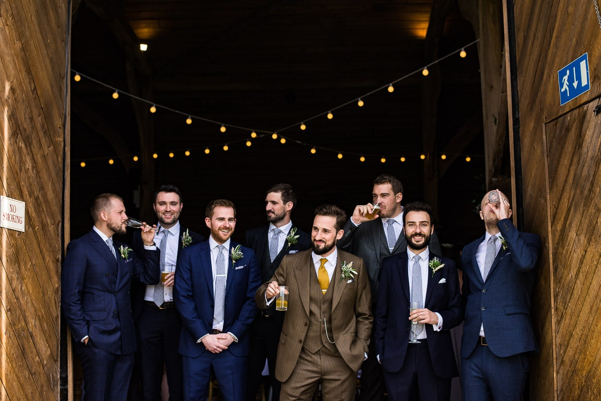 groom and groomsmen drinking and posing for the camera