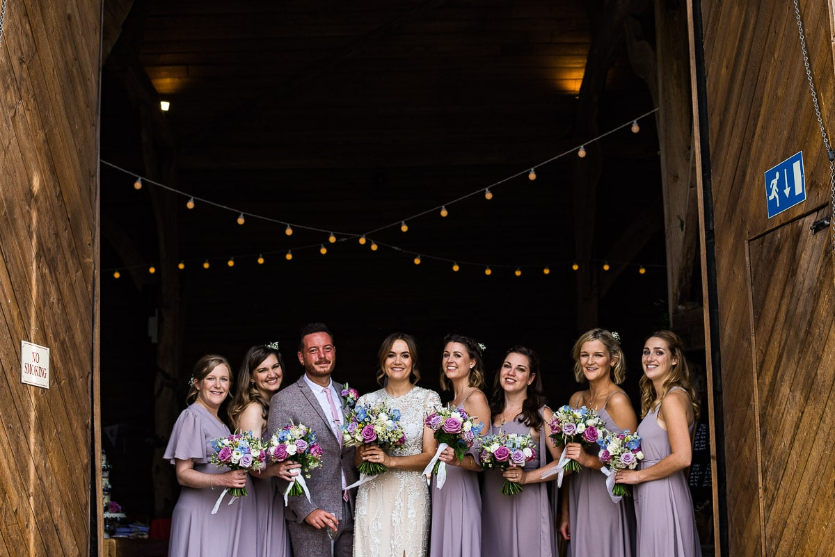 bridesmaids pose with bride and groom with bouquets by moody blooms