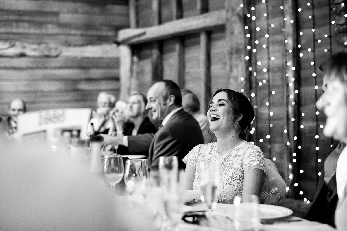 bride laughs at wedding speech while sat at dinner table