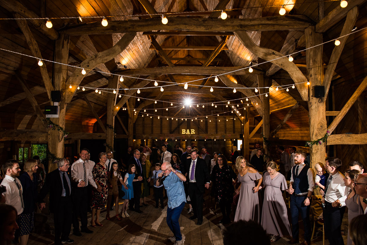 wedding guests watch as guest entertains them by teaching them how to barn dance
