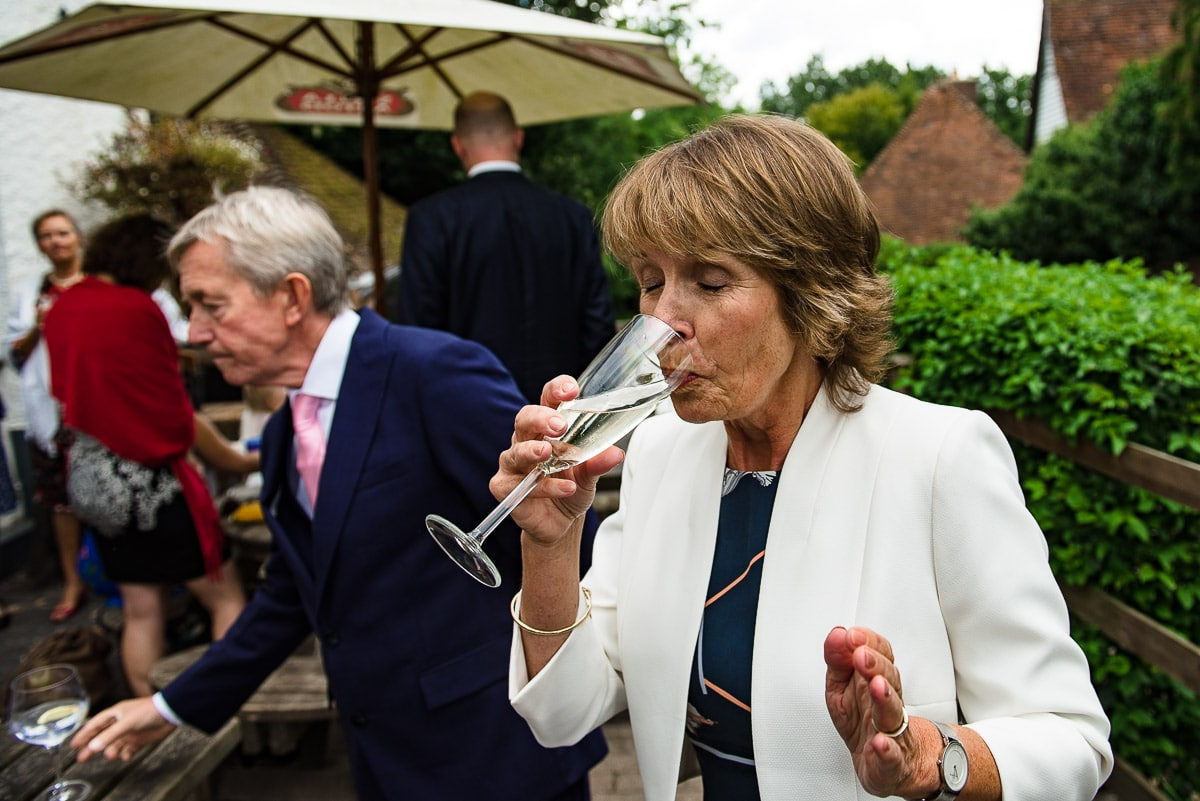 wedding guest sips on champagne as guests enjoy the weather