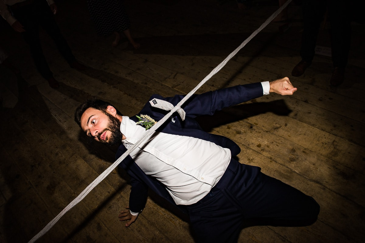 wedding guest plays limbo under makeshift tie limbo pole