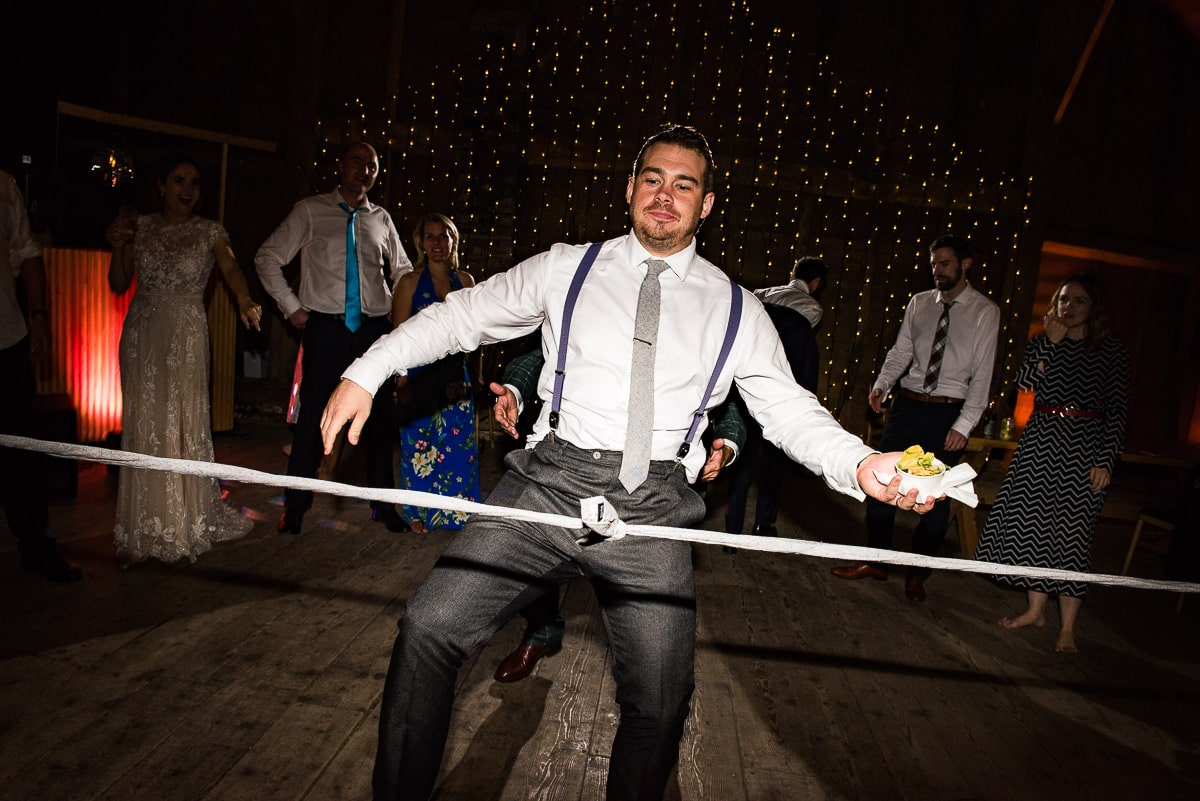 wedding guest plays limbo with food in one hand and balancing himself with the other