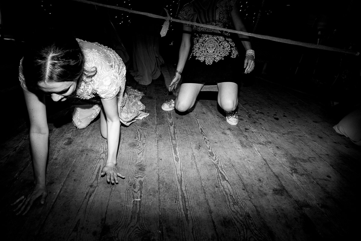 wedding guests cheat in a game of limbo by crawling