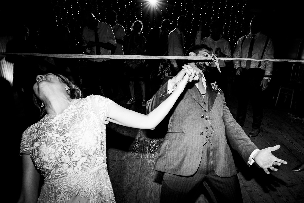 bride and groom celebrate wedding with traditional limbo