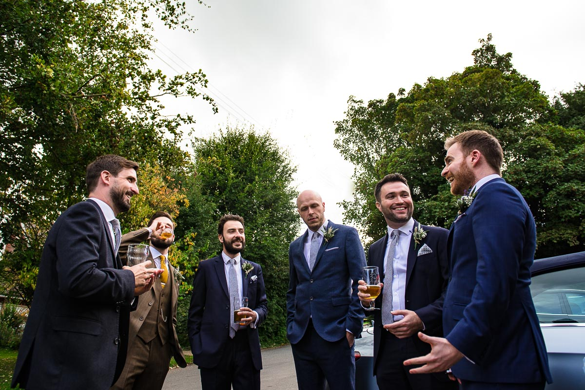groom and groomsmen chat and have a drink outside