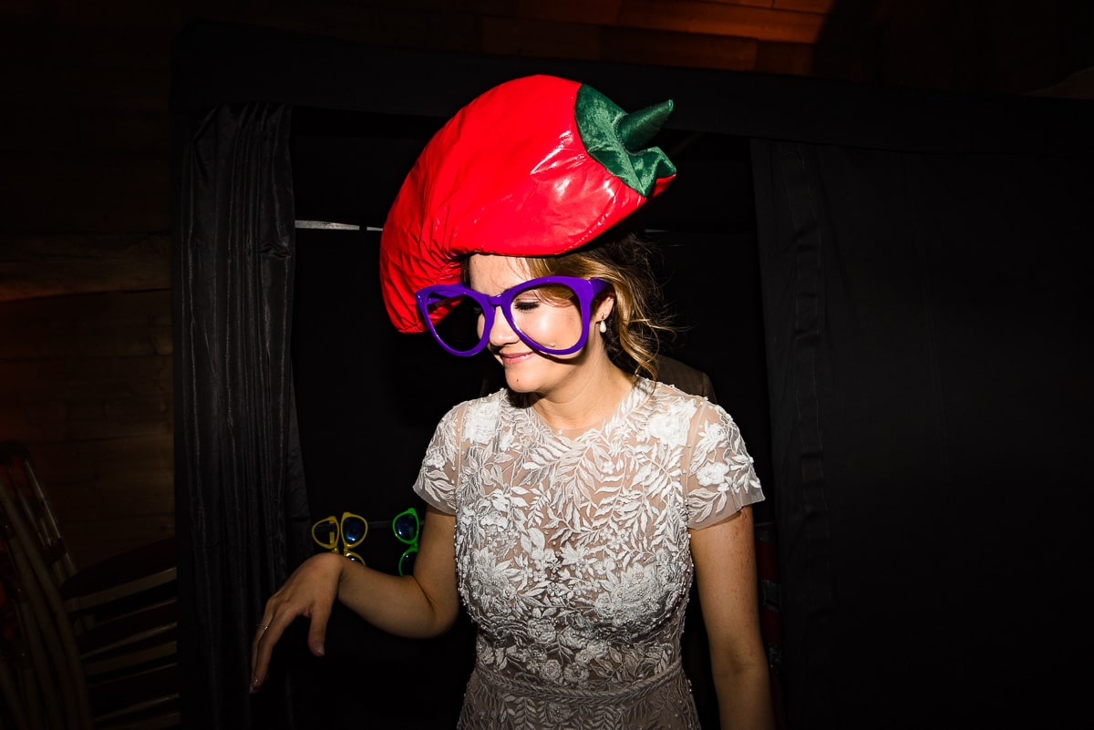candid wedding guest enjoys the fun accessories with big glasses and chilly hat