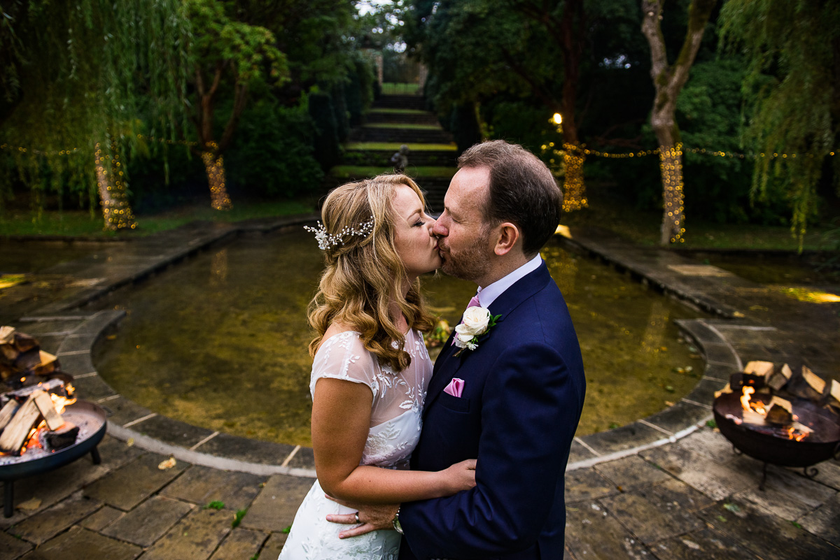 bride and groom embrace by Cornwell manor pond