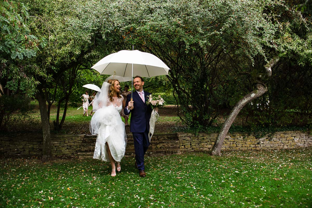 bride and groom stroll with parasol through Cornwell manor's garden