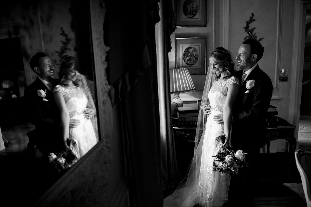 bride and groom cuddle by window inside Cornwell Manor