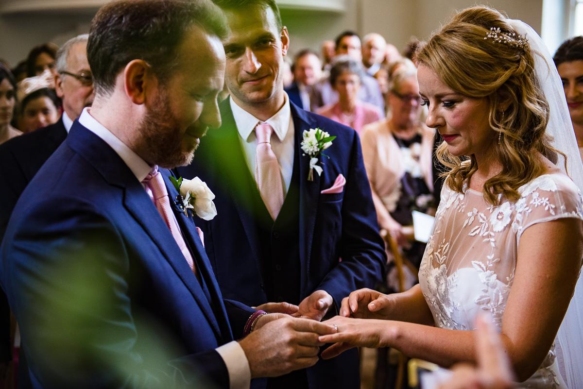 groom puts wedding ring onto brides finger at Cornwell Manor alter