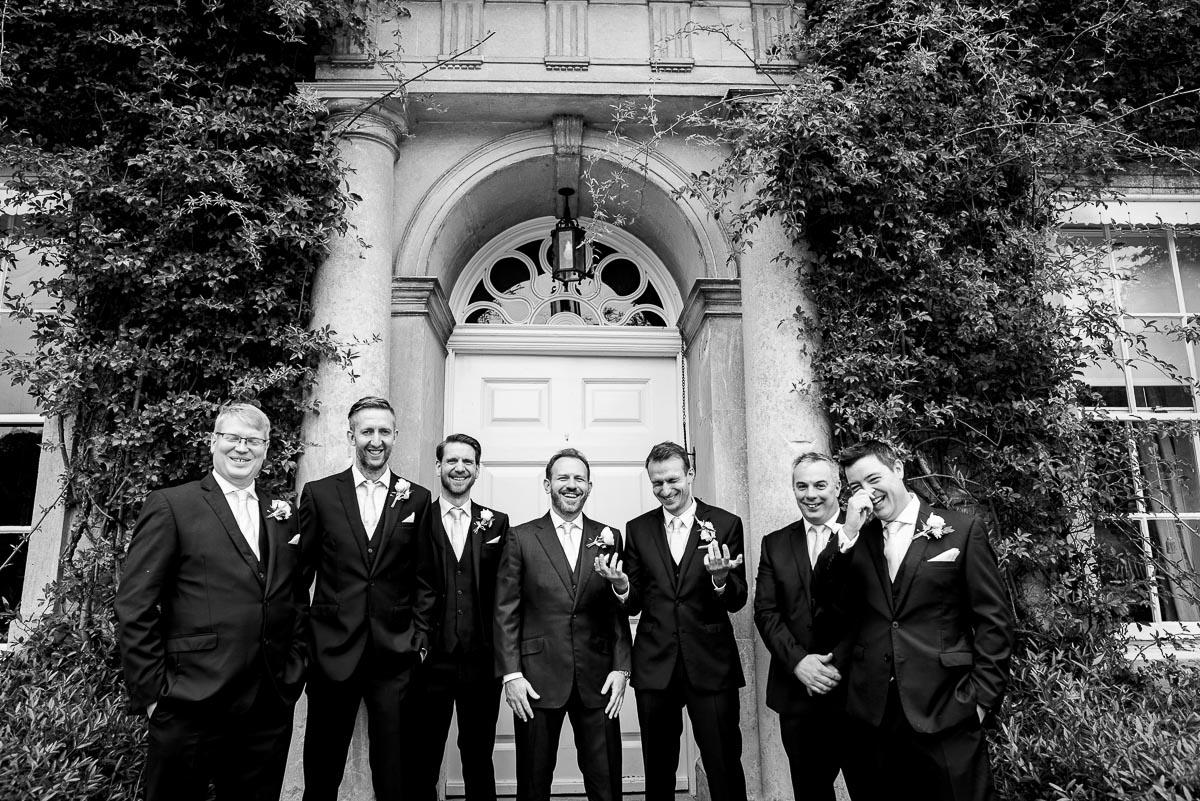 groomsmen pose in group outside Cornwell manor