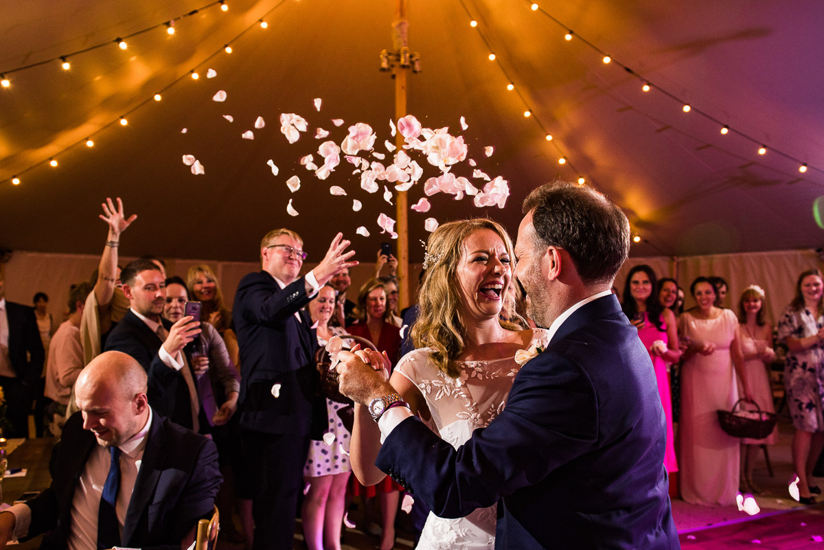 guests throw flower petals over bride and groom