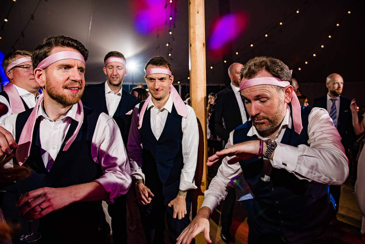 groomsmen party on the dancefloor with ties on their heads