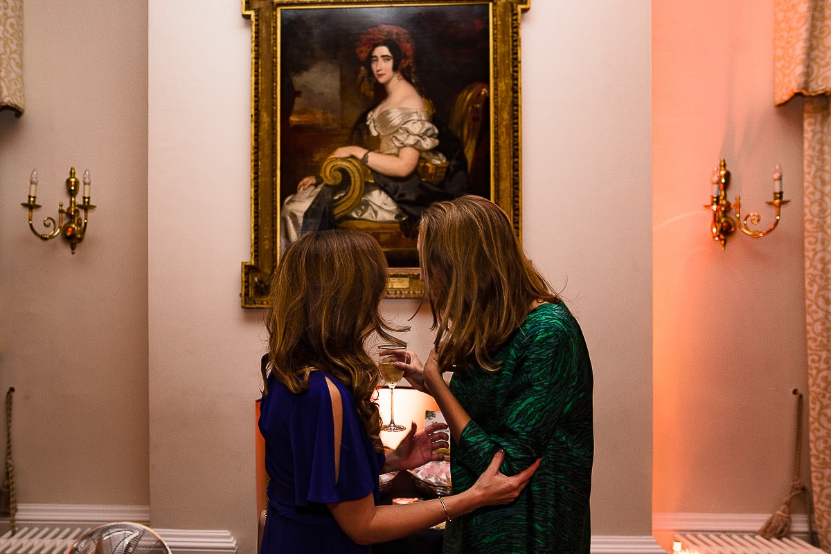 wedding guests chat in front of ancient oil portrait painting at Kew gardens