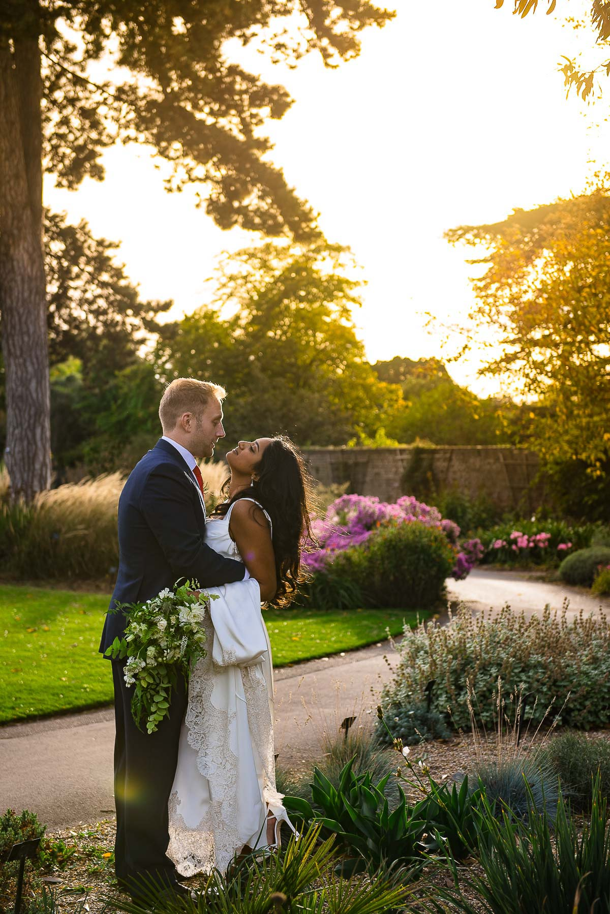 bride and groom embrace as sun sets in Cambridge cottage gardens London