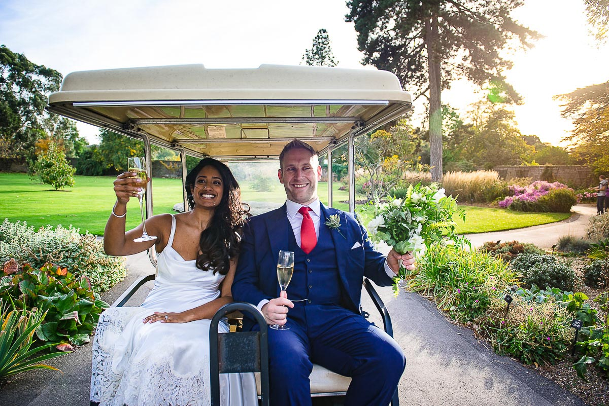 Couple with drinks and bouquet on the back of golf cart at Kew Gardens London