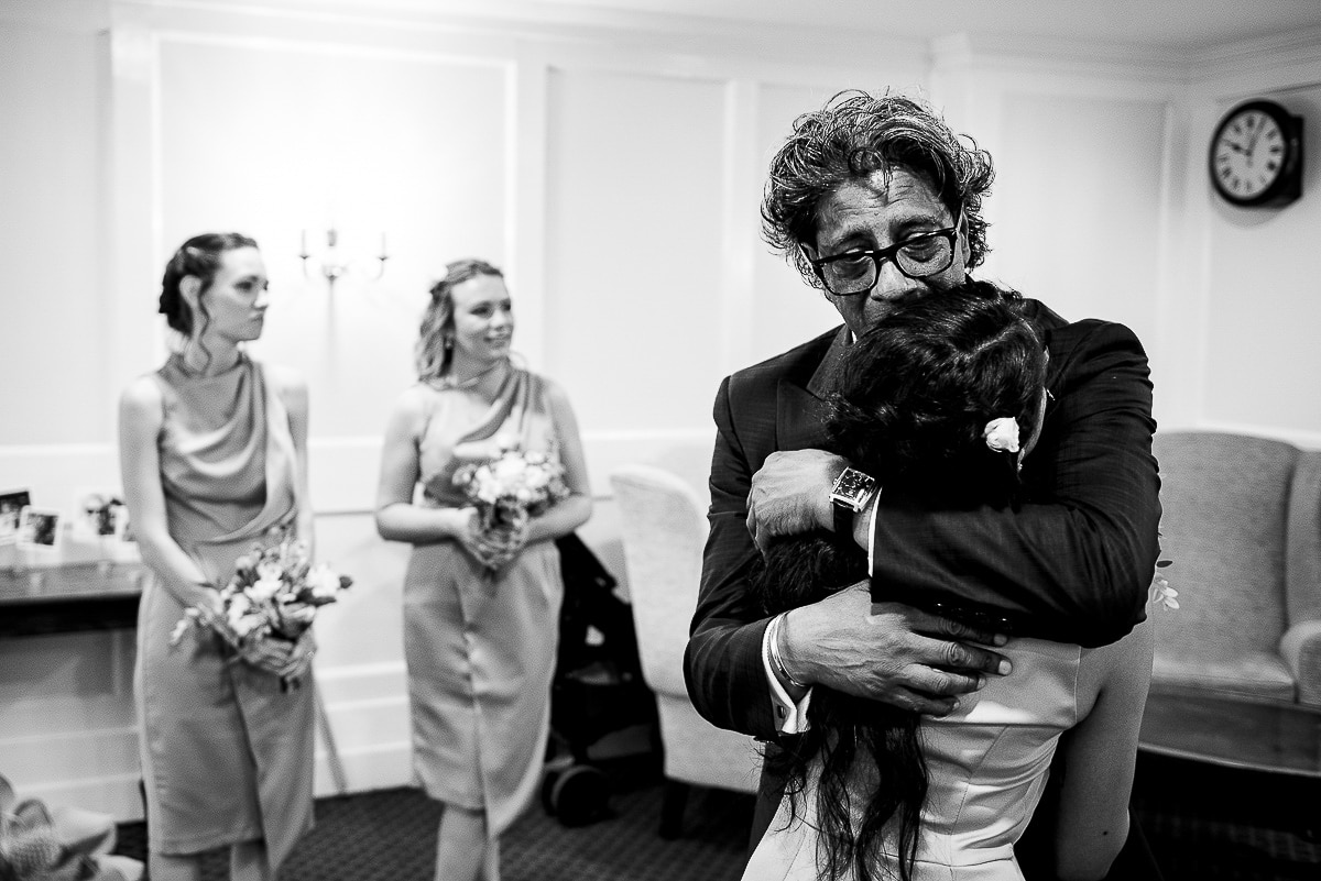 bridesmaid and father of the bride emotional embrace