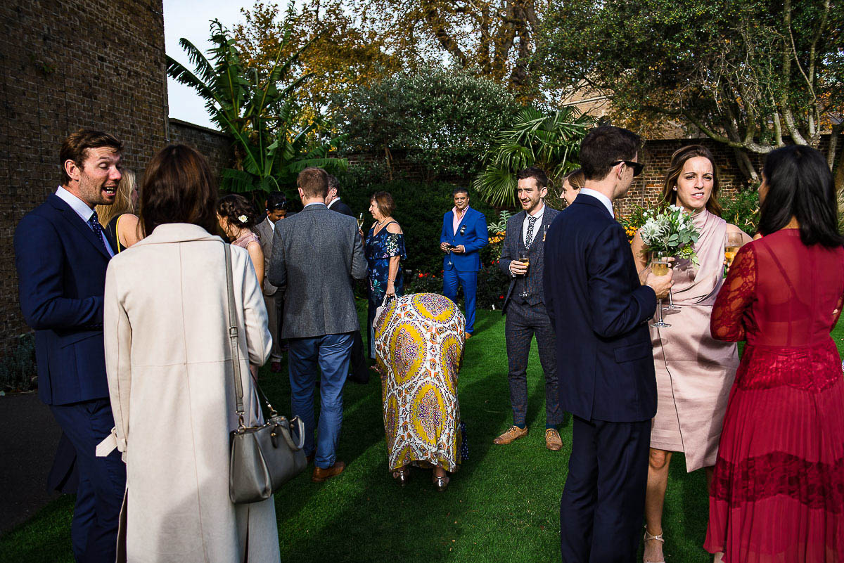 wedding guests mingle and chat in garden at Cambridge Cottage Kew Gardens