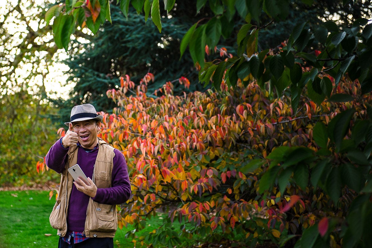Kew Gardens tourist thumbs up for camera amidst colourful foliage