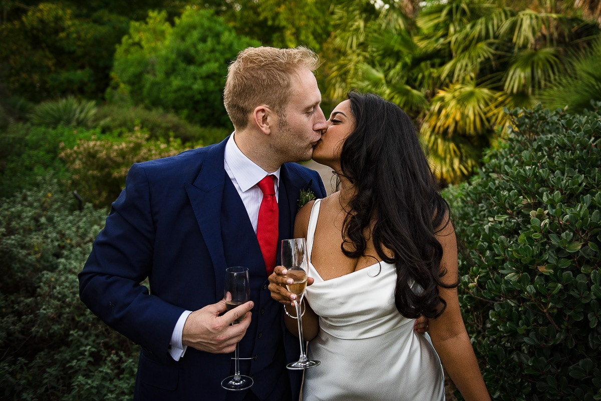 bride and groom kiss with champagne outside cambridge cottage Kew Gardens in London