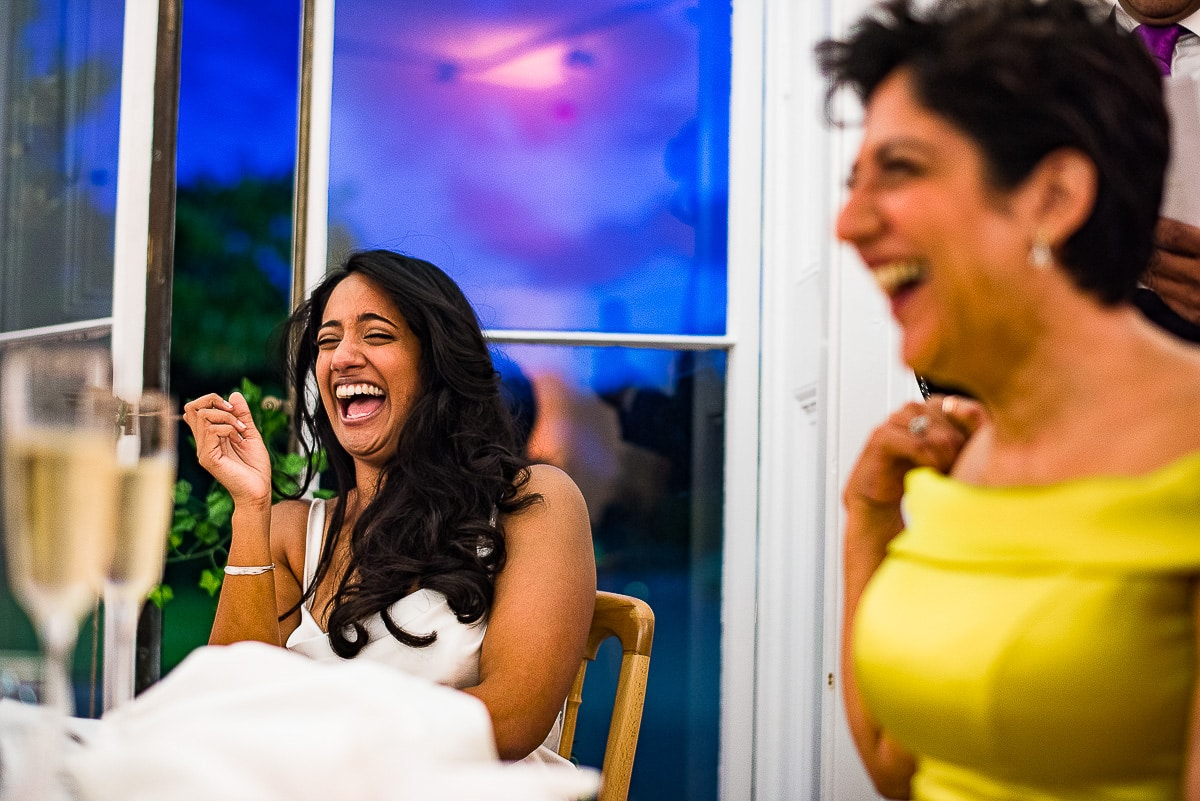 bride laughs at funny wedding speech