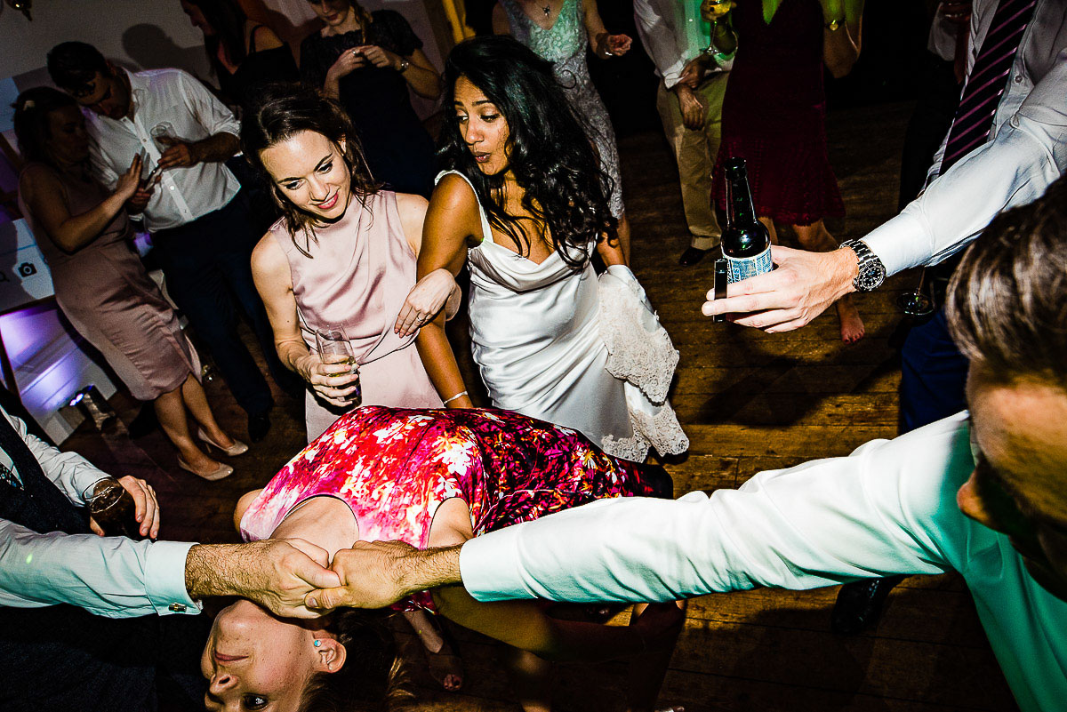wedding guests cheer on dancefloor as guest does the limbo