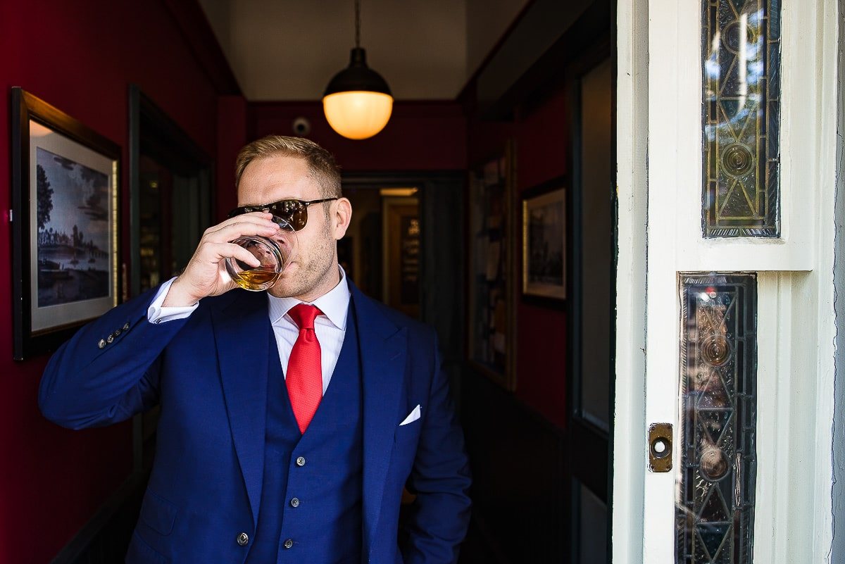 groom drinks whiskey wearing sunglasses and red tie