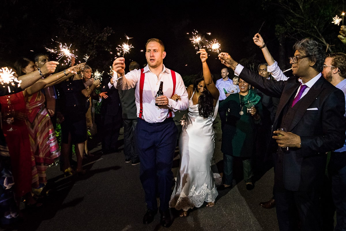 wedding guests celebrate with sparklers at night