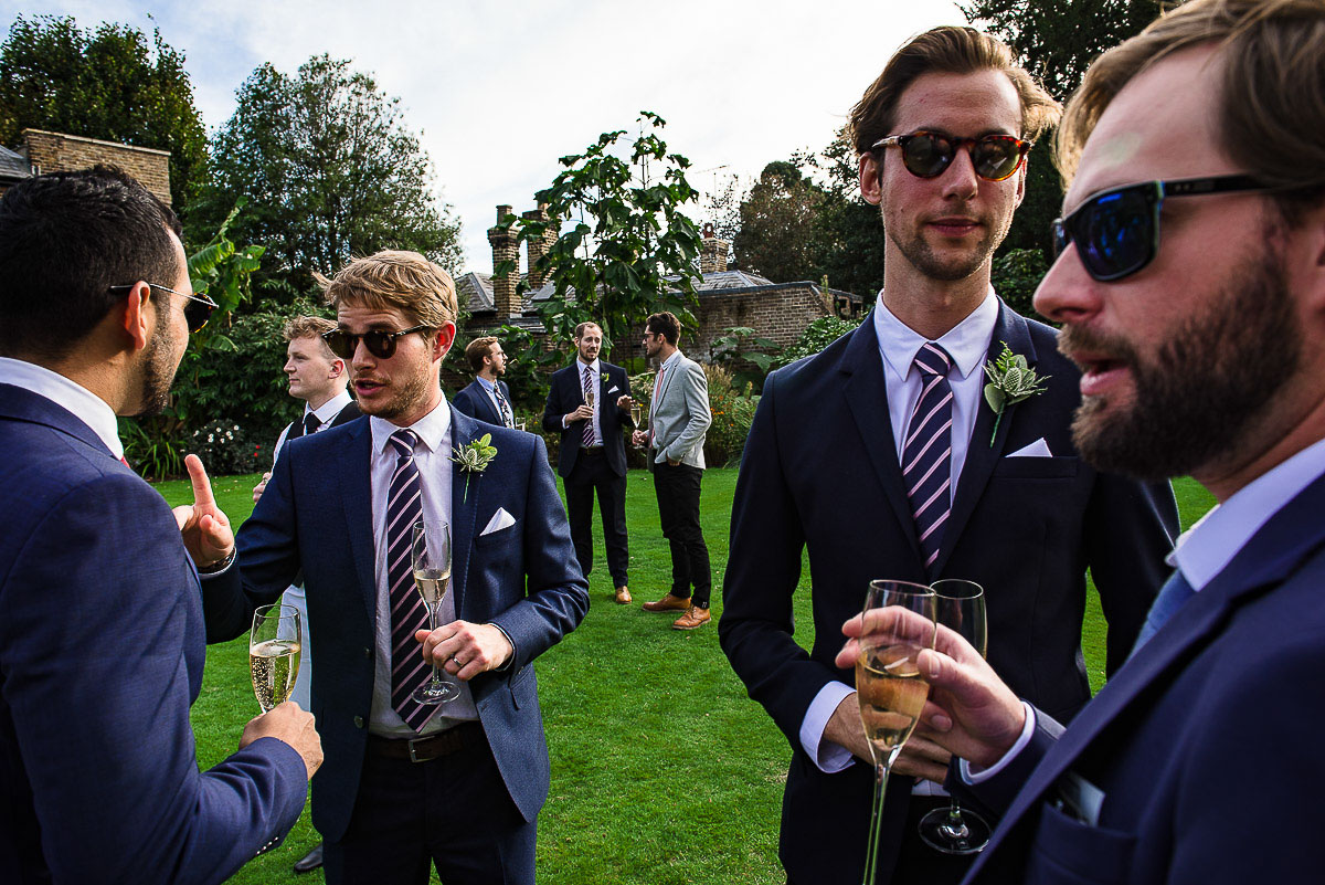 groomsmen and guests interact outside cambridge cottage wedding reception