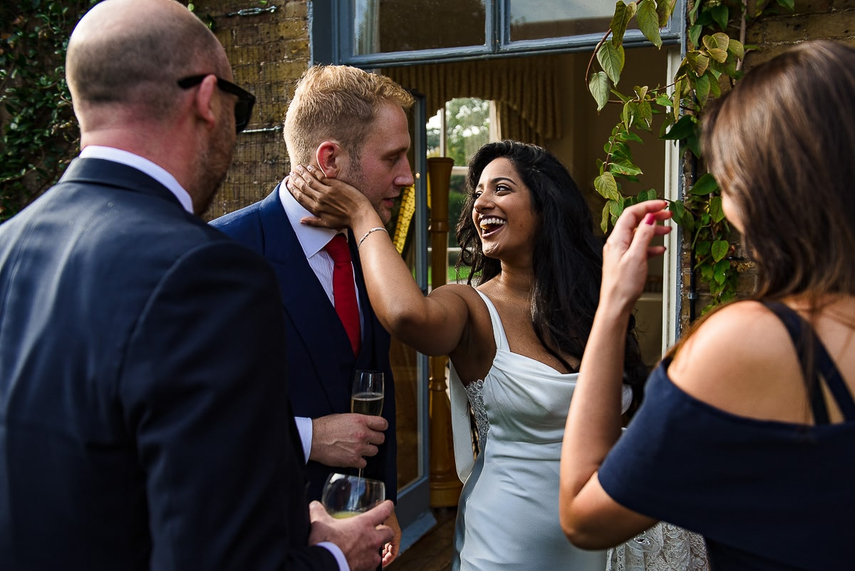 bride laughs and tenderly holds groom at London wedding