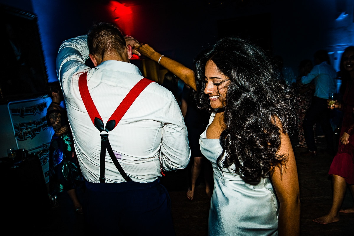 bride and groom with red braces dance on the dancefloor