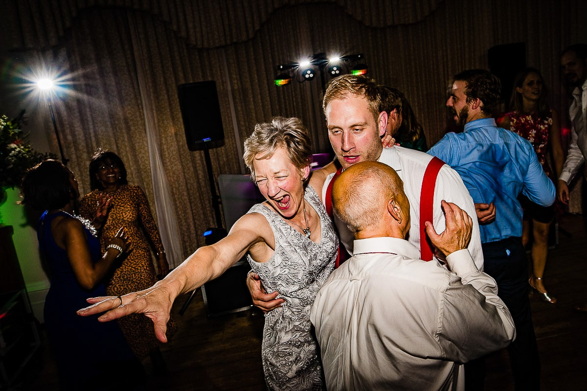 groom with his drunk parents on the dance floor