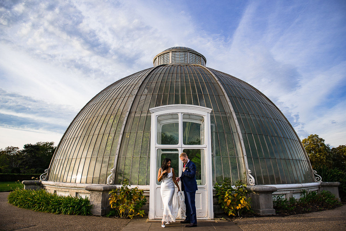 bride and groom outside domed greenhouse in Kew gardens