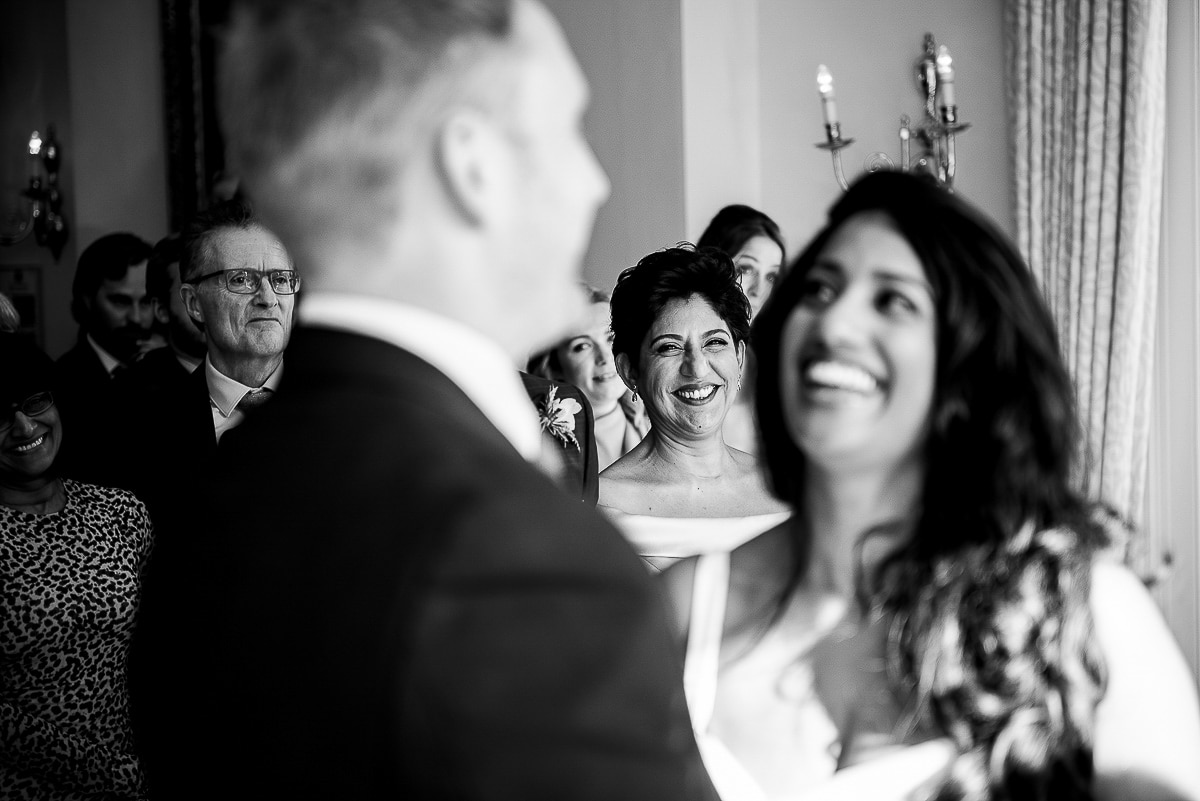 wedding guests look on and smile at the couple saying their vows