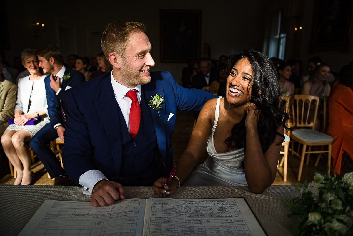 bride and groom laugh as they sign wedding register